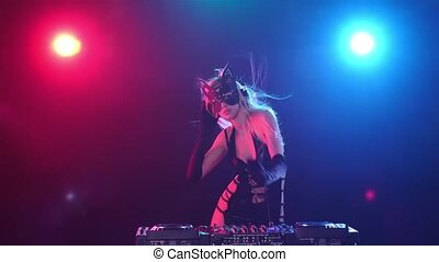 Blonde longhair woman dj in erotic dress and kitty mask,...