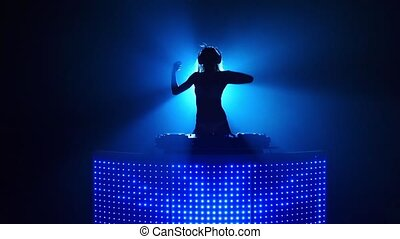 Blond girl dj sexy dancing in blue silhouette. Slow motion -...