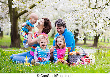 Family with children enjoying picnic in spring park