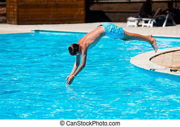 Boy diving in swimming pool - Active teenager boy jumping...