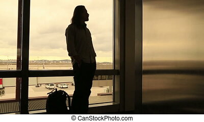 Man waiting at the airport - Passenger waiting to board a...