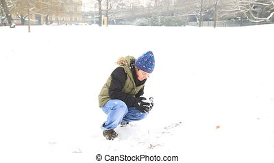 Happy child boy playing with a snow on a snowy winter park