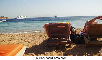 Woman Sunbathing on a Lounger Overlooking the Red Sea -...