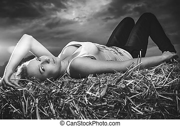girl lying on haystack stormy sky in the background -...