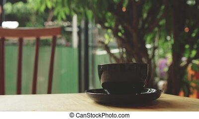 Young woman stirring coffee cup in the cafe