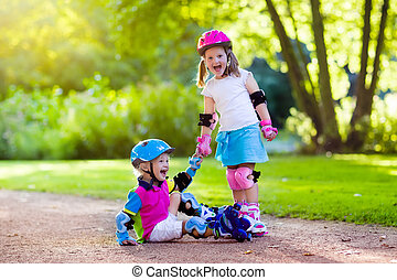 Kids roller skating in summer park - Girl and boy learn to...