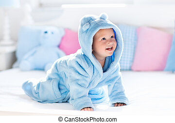 Baby in bathrobe or towel after bath - Cute happy laughing...