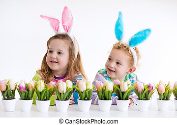 Kids with bunny ears on Easter egg hunt - Happy children...