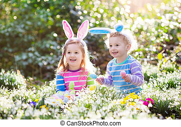 Kids on Easter egg hunt in blooming spring garden. Children...