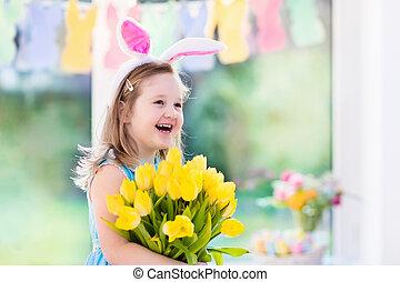 Little girl in bunny ears on Easter egg hunt - Happy little...