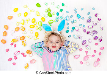 Child on Easter egg hunt. Pastel rainbow eggs. - Funny...