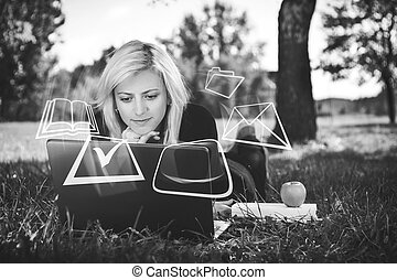 student studying in park with laptop