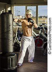 Shirtless young man kicking punching bag