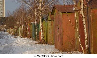 Old little car garages in winter, handheld shot. Eastern...