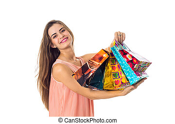 happy girl raised in the hands of colored packets with gifts and smiling isolated on white background