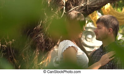 A beautiful young couple, a pleasant conversation in the park, looking at each other in the garden with herbs