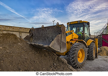 day view of yellow excavator with shovel at construction...