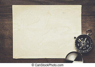 compass and old paper on the brown wooden table background