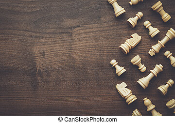 chess figures on brown wooden table background - chess...