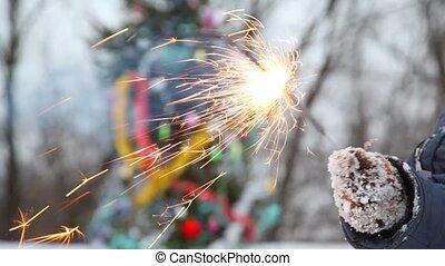 Childs hand holds burning sparkler against Christmas tree -...