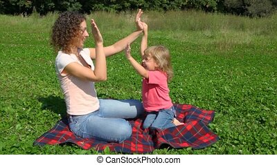 mother with daugher plays pat-a-cake sits outdoor in field -...
