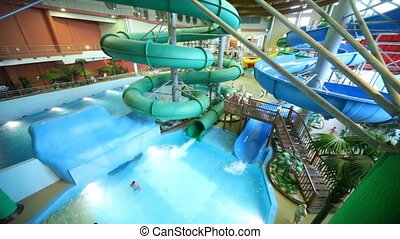 People bathe in two big pools  with a fountains and slip on inflatable rings in indoor water park