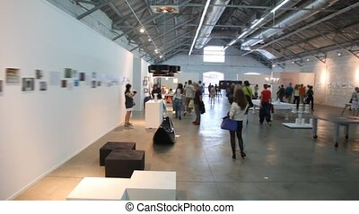 people walks and stands in exhibition hall, panning