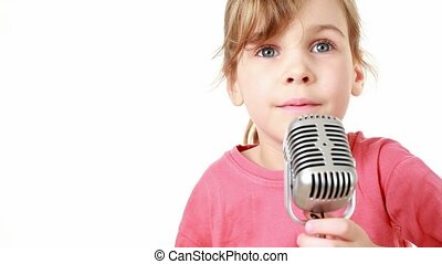 girl twitches and sings in microphone - A little girl in a...