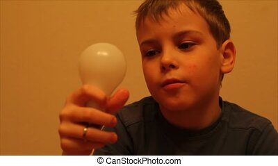 boy in blue T-shirt switchs on and off a light bulb - Little...