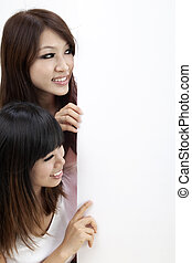 Two girls and blank sign - Two attractive young asian women...