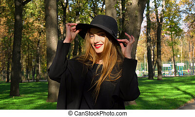 young woman with red lips in stylish coat and hat