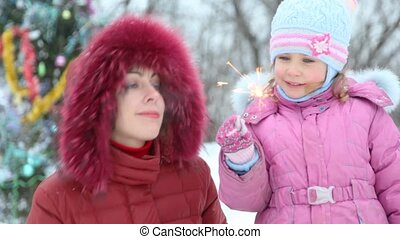 Mother and her daughter with sparkler against christmas tree...
