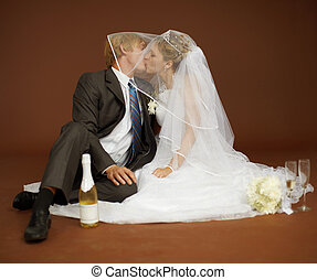 Bride and groom kissing - The bride and groom kissing and...