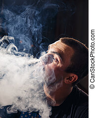 Young man vaping an electronic cigarette in dark