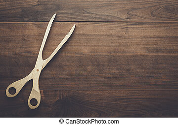 wooden grill tongs on the table - wooden grill tongs on the...