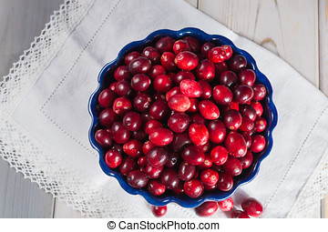 Fresh cranberries in a blue bowl. Ripe berries of Vaccinium...