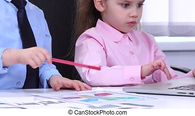 Children businessmen looking at the charts and diagravy...