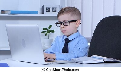 Boy in glasses is typing on a laptop and the data recorded...
