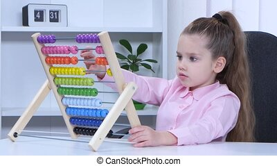 Little girl in shirt sitting at the table and said to the multicolored aba