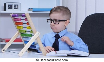 Baby boy with glasses considers the accounts and wrote in a...