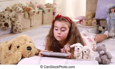Child playing on a tablet - Blond young child playing on a...