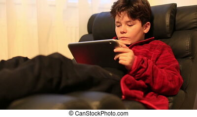 Portrait of young boy using digital tablet at home - Child...