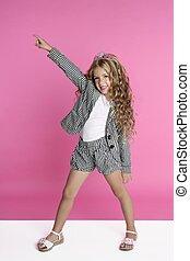 dancing full length little girl on pink studio background