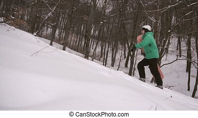 Snowboarder Walks Snow Slope - Young attractive snowboarder...
