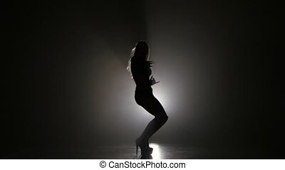 Silhouette of woman posing in studio on dark background,...