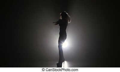 Longhaired blonde girl dancing on high heels. Dark smoke...
