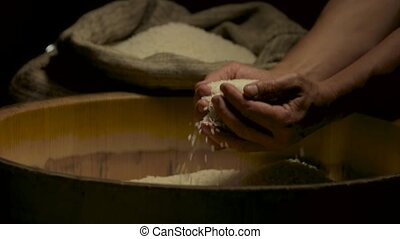 Rice and hands of man. Sack with white groats.