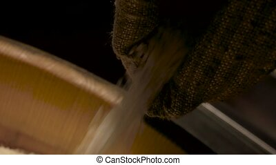 Rice falling from sack. Closeup of raw groats. Grains of top...