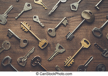 many different keys on wooden table - overhead of many...