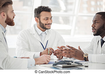 Smiling doctor discussing with affiliates during meeting -...